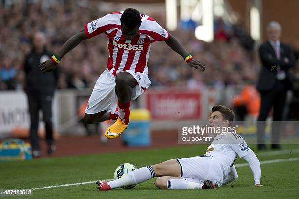 Swansea City's English midfielder Tom Carroll vies with Stoke City's Senegalese striker Mame Biram Diouf during the English Premier League football...