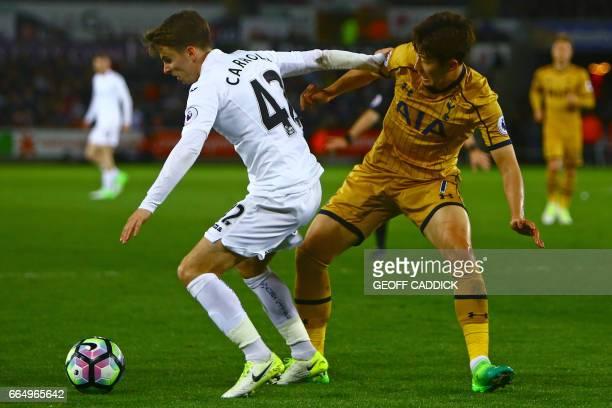 Swansea City's English midfielder Tom Carroll vies with Tottenham Hotspur's South Korean striker Son HeungMin during the English Premier League...