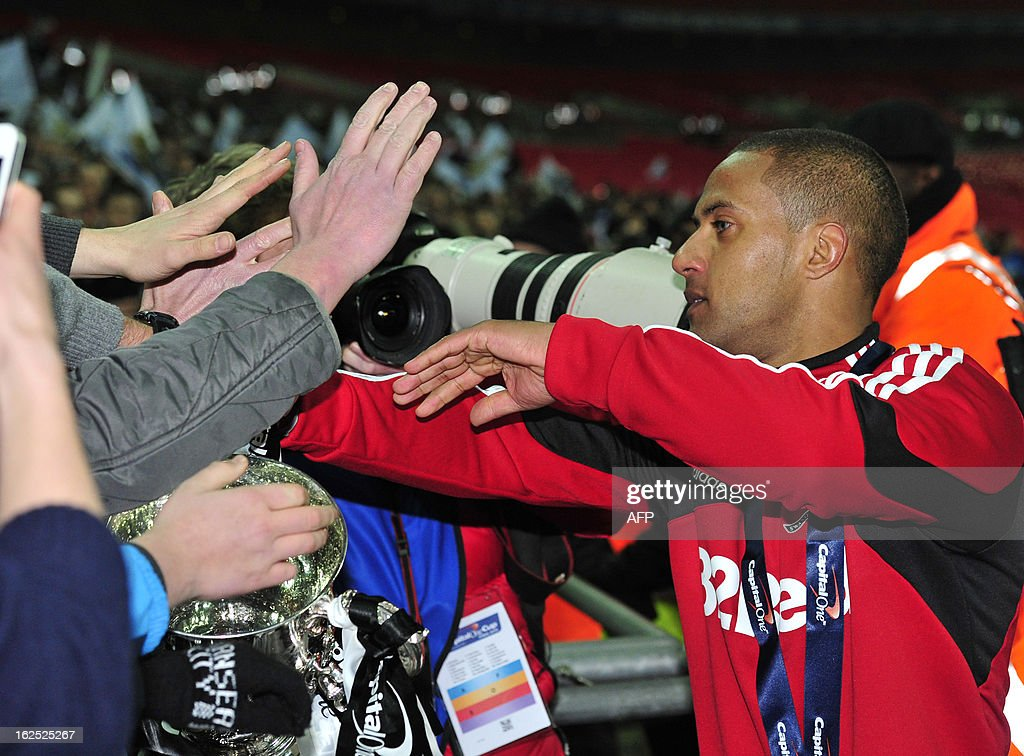 "Swansea City's English midfielder Wayne Routledge (R) with supporters after the League Cup final football match between Bradford City and Swansea City at Wembley Stadium in London, England on February 24, 2013. Swansea City won the game 5-0. AFP PHOTO/GLYN KIRK USE. No use with unauthorized audio, video, data, fixture lists, club/league logos or ""live"" services. Online in-match use limited to 45 images, no video emulation. No use in betting, games or single club/league/player publications."