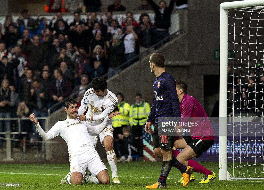 "Swansea City's English striker Danny Graham (L) celebrates scoring their second goal to equalise late in the game with teammate Ki Sung-Yueng (2nd L) against Arsenal during the FA Cup third round football match at the Liberty Stadium in Swansea, Wales, on January 6, 2013. The game ended with a 2-2 draw. AFP PHOTO / ADRIAN DENNIS USE. No use with unauthorized audio, video, data, fixture lists, club/league logos or ""live"" services. Online in-match use limited to 45 images, no video emulation. No use in betting, games or single club/league/player publications."