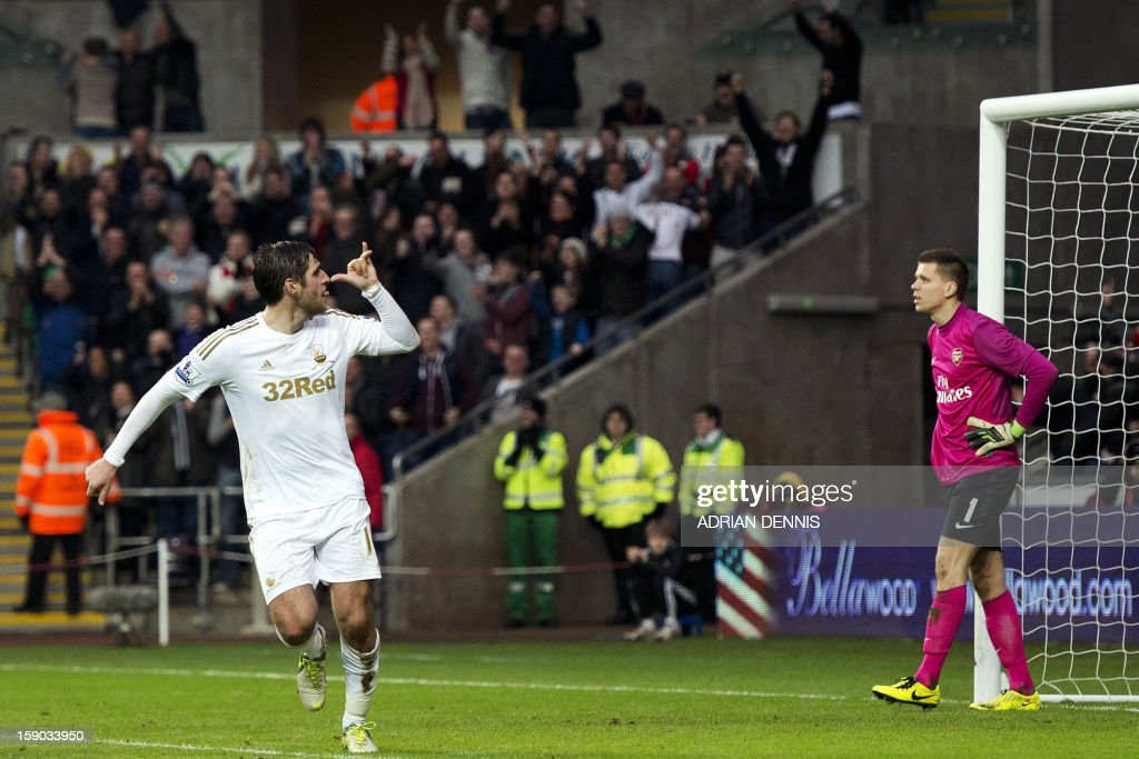 "Swansea City's English striker Danny Graham (L) gestures after scoring a late goal to equalise while Arsenal's Polish goalkeeper Wojciech Szczesny (R) looks on during the FA Cup third round football match at the Liberty Stadium in Swansea, Wales, on January 6, 2013. The game ended with a 2-2 draw. USE. No use with unauthorized audio, video, data, fixture lists, club/league logos or ""live"" services. Online in-match use limited to 45 images, no video emulation. No use in betting, games or single club/league/player publications"