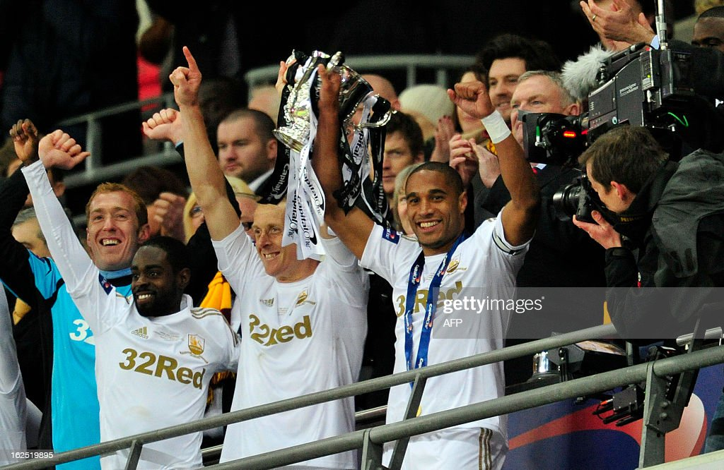 Swansea City's English-born Welsh defender Ashley Williams (R) lifts the trophy with Swansea City's English defender Garry Monk (C), man of the match Swansea City's English midfielder Nathan Dyer (L) after the League Cup final football match between Bradford City and Swansea City at Wembley Stadium in London, England on February 24, 2013. Dyer scored twice as Swansea City won the game 5-0. AFP PHOTO/GLYN KIRK USE. No use with unauthorized audio, video, data, fixture lists, club/league logos or live services. Online in-match use limited to 45 images, no video emulation. No use in betting, games or single club/league/player publications. / AFP / GLYN