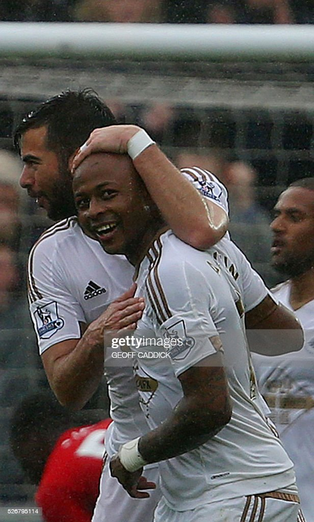 Swansea City's Ghanaian striker Andre Ayew (R) celebrates scoring their third goal during the English Premier League football match between Swansea City and Liverpool FC at the Liberty Stadium, in Swansea, South Wales, on May 1, 2016. / AFP / GEOFF CADDICK / RESTRICTED TO EDITORIAL USE. No use with unauthorized audio, video, data, fixture lists, club/league logos or 'live' services. Online in-match use limited to 75 images, no video emulation. No use in betting, games or single club/league/player publications. /