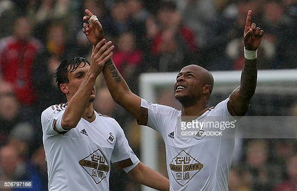 Swansea City's Ghanaian striker Andre Ayew celebrates scoring their third goal with Swansea City's English midfielder Jack Cork during the English...
