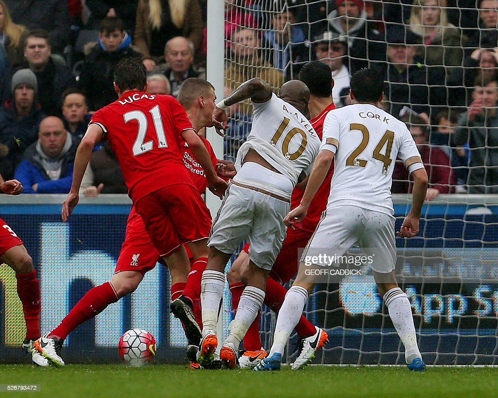 Swansea City's Ghanaian striker Andre Ayew (C) scores their third goal during the English Premier League football match between Swansea City and Liverpool at the Liberty Stadium, in Swansea, South Wales, on May 1, 2016. / AFP / GEOFF CADDICK / RESTRICTED TO EDITORIAL USE. No use with unauthorized audio, video, data, fixture lists, club/league logos or 'live' services. Online in-match use limited to 75 images, no video emulation. No use in betting, games or single club/league/player publications. /