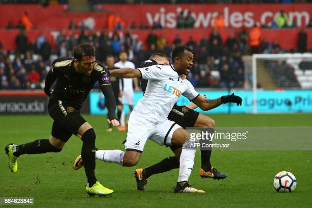Swansea City's Ghanaian striker Jordan Ayew vies with Leicester City's Austrian defender Christian Fuchs and Leicester City's English midfielder Marc...
