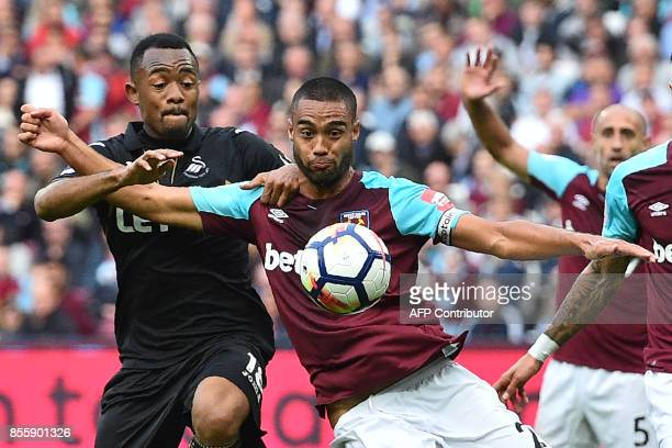 Swansea City's Ghanaian striker Jordan Ayew vies with West Ham United's New Zealand defender Winston Reid during the English Premier League football...