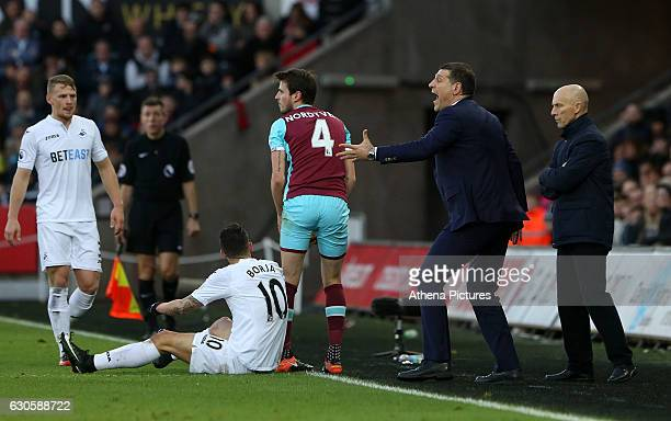 Swansea Citys head coach Bob Bradley watches on as West Ham United Manager Slaven Bilic becomes frustrated as Swansea win a free kick after Havard...