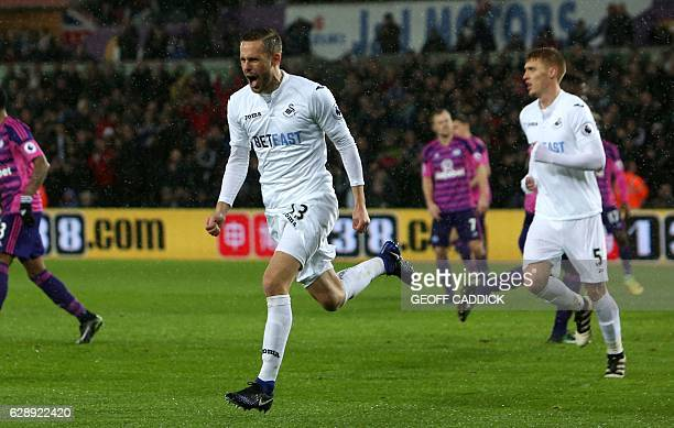 Swansea City's Icelandic midfielder Gylfi Sigurdsson celebrates after scoring the opening goal from the penalty spot during the English Premier...