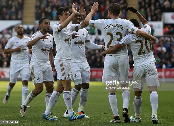 Swansea City's Icelandic midfielder Gylfi Sigurdsson celebrates scoring his team's first goal with teammates during the English Premier League...