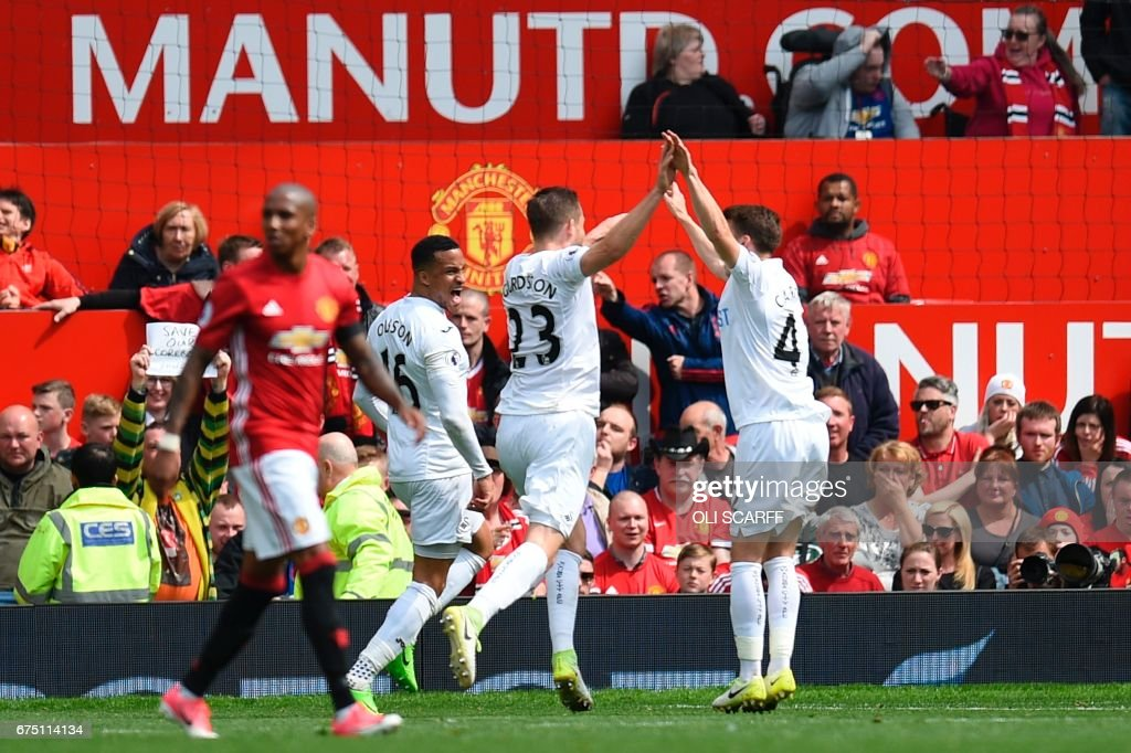 Swansea City's Icelandic midfielder Gylfi Sigurdsson (C) celebrates scoring their first goal to equalise 1-1 during the English Premier League football match between Manchester United and Swansea City at Old Trafford in Manchester, north west England, on April 30, 2017. / AFP PHOTO / Oli SCARFF / RESTRICTED TO EDITORIAL USE. No use with unauthorized audio, video, data, fixture lists, club/league logos or 'live' services. Online in-match use limited to 75 images, no video emulation. No use in betting, games or single club/league/player publications. /