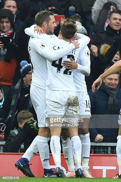 Swansea City's Icelandic midfielder Gylfi Sigurdsson hugs teammates after scoring their third goal during the English Premier League football match...