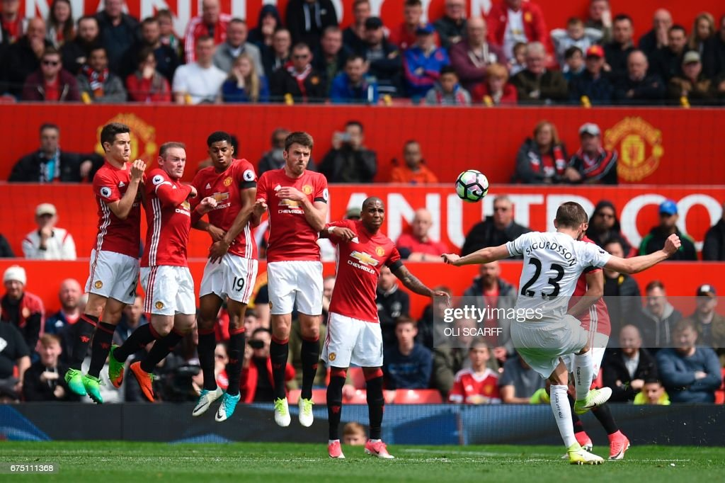 Swansea City's Icelandic midfielder Gylfi Sigurdsson (R) scores from a free kick to equalise 1-1 during the English Premier League football match between Manchester United and Swansea City at Old Trafford in Manchester, north west England, on April 30, 2017. / AFP PHOTO / Oli SCARFF / RESTRICTED TO EDITORIAL USE. No use with unauthorized audio, video, data, fixture lists, club/league logos or 'live' services. Online in-match use limited to 75 images, no video emulation. No use in betting, games or single club/league/player publications. /