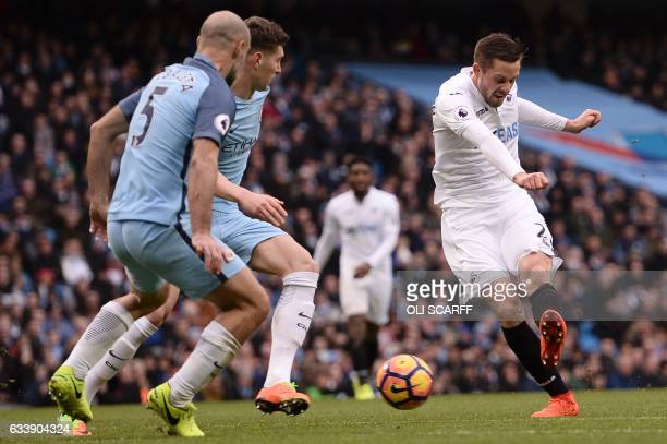 Swansea City's Icelandic midfielder Gylfi Sigurdsson shoots to score their first goal during the English Premier League football match between...
