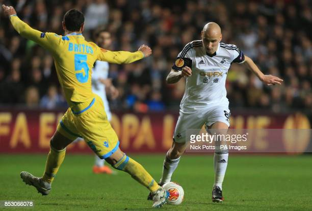 Swansea City's Jonjo Shelvey skips over tackle by Napoli's Miguel Britos during the UEFA Europa League Round of 32 match at the Liberty Stadium...