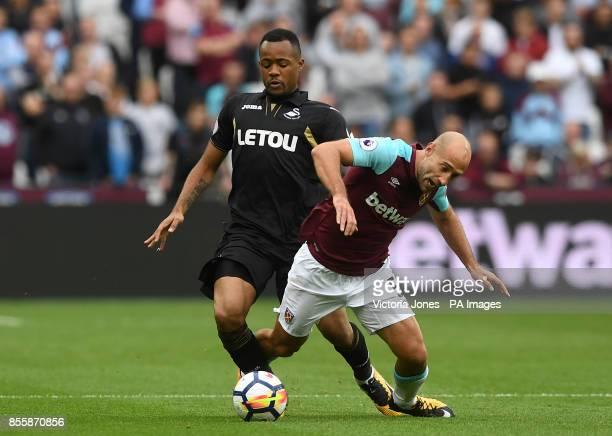 Swansea City's Jordan Ayew and West Ham United's Pablo Zabaleta battle for the ball during the Premier League match at London Stadium