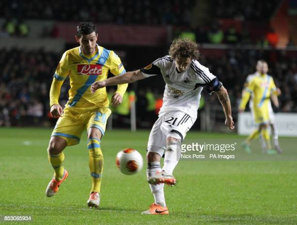 Swansea City's Jose Canas has a shot at goal watched by Napoli's Blerim Dzemaili during the UEFA Europa League Round of 32 match at the Liberty...