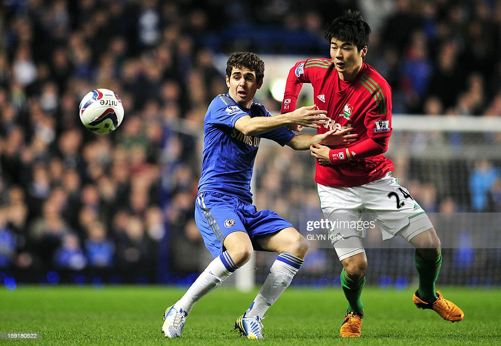 """Swansea City's Korean midfielder Ki Sung-Yueng (R) vies with Chelsea's Brazilian midfielder Oscar (L) during the English League Cup first leg semi-final football match between Chelsea and Swansea City at Stamford Bridge in London on January 9, 2013. USE. No use with unauthorized audio, video, data, fixture lists, club/league logos or """"live"""" services. Online in-match use limited to 45 images, no video emulation. No use in betting, games or single club/league/player publications."""