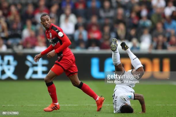 Swansea City's Kyle Naughton lands on his head after clashing with Huddersfield Town's Rajiv van La Parra during the Premier League match at the...