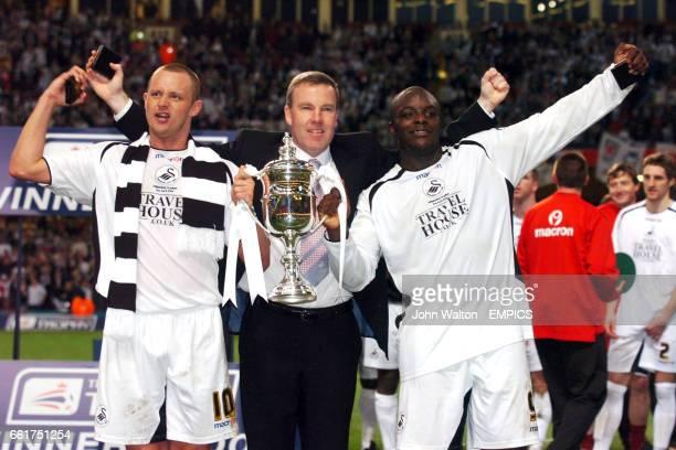 Swansea City's manager Kenny Jackett celebrates with the goalscorers Lee Trundle and Adebayo Akinfenwa