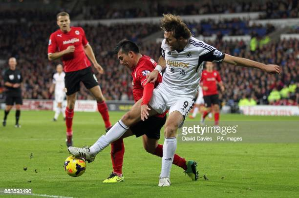 Swansea City's Michu challenges Cardiff City's Gary Medel during the Barclays Premier League match at Cardiff City Stadium Cardiff