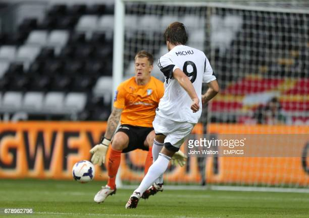 Swansea City's Michu slides the ball past Malmo's goalkeeper Johan Dahlin to score the opening goal of the game