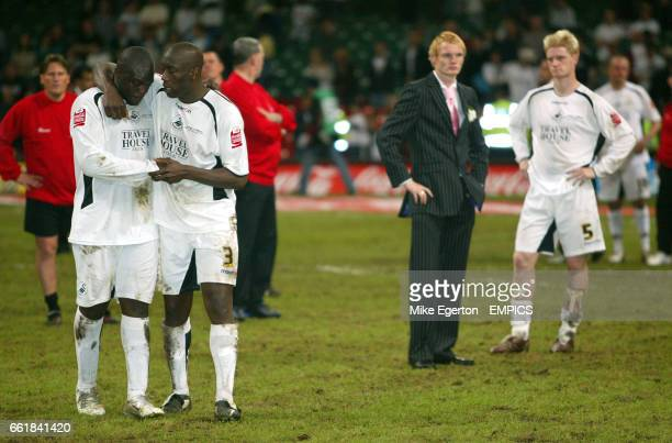Swansea City's missed penalty takers Adebayo Akinfenwa is consoled by Kevin Austin as Alan Tate stands dejected behind them