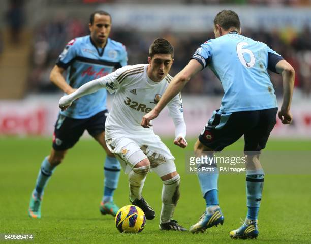 Swansea City's Pablo Hernandez and Queens Park Rangers' Clint Hill battle for the ball