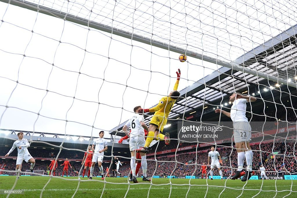 Swansea City's Polish goalkeeper Lukasz Fabianski (C) dives for a ball that went over the bar during the English Premier League football match between Liverpool and Swansea City at Anfield in Liverpool, north west England on January 21, 2017. / AFP / Anthony DEVLIN / RESTRICTED TO EDITORIAL USE. No use with unauthorized audio, video, data, fixture lists, club/league logos or 'live' services. Online in-match use limited to 75 images, no video emulation. No use in betting, games or single club/league/player publications. /