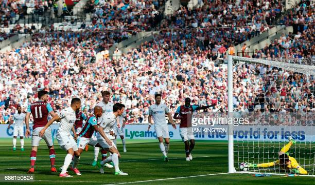 Swansea City's Polish goalkeeper Lukasz Fabianski stops the ball on the goal line to make a save from a West Ham United's Scottish midfielder Robert...