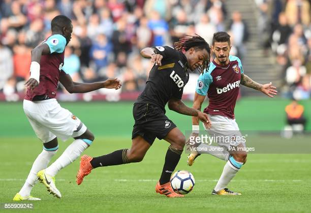 Swansea City's Renato Sanches in aciton with West Ham United's Cheikhou Kouyate and Manuel Lanzini during the Premier League match at London Stadium
