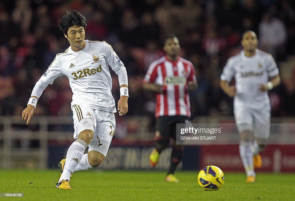 """Swansea City's South Korean midfielder Ki Sung-Yeung (L) passes the ball during the English Premier League football match between Sunderland and Swansea City at The Stadium of Light in Sunderland, north-east England on January 29, 2013. The game finished 0-0. USE. No use with unauthorized audio, video, data, fixture lists, club/league logos or """"live"""" services. Online in-match use limited to 45 images, no video emulation. No use in betting, games or single club/league/player publications"""