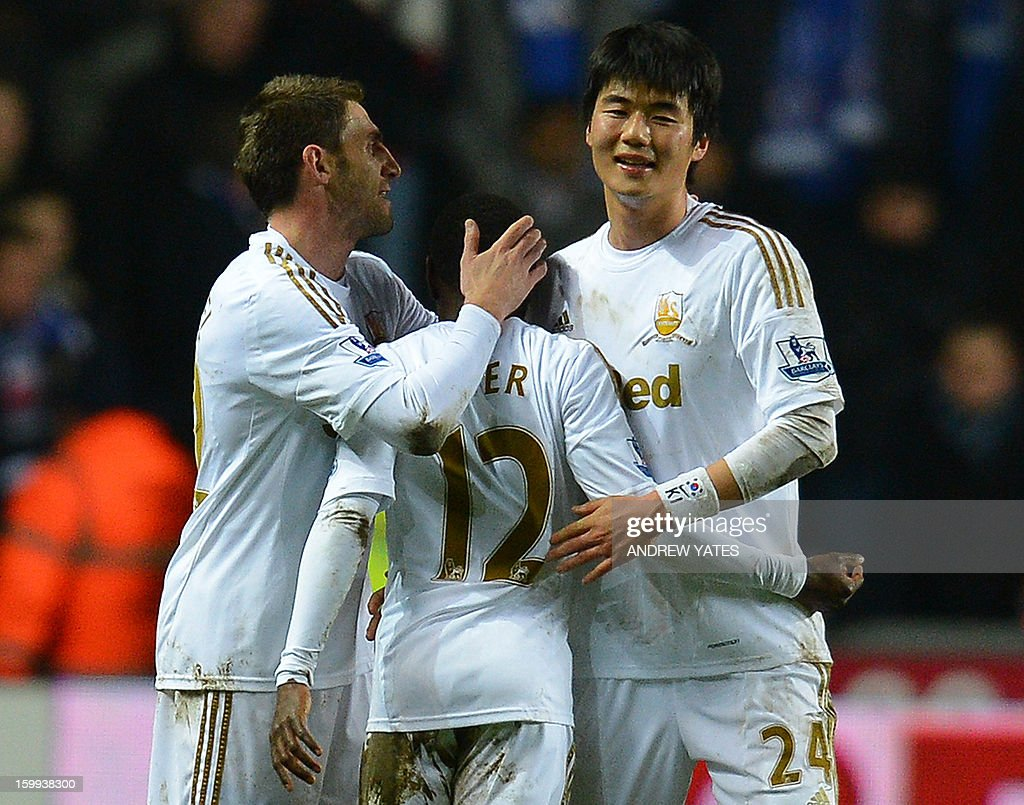 """Swansea City's South Korean midfielder Ki Sung-Yueng (R) celebrates with Swansea City's Spanish defender Angel Rangel (L) and Swansea's English forward Nathan Dyer at the final whistle of the English League Cup semi-final second leg football match between Swansea City and Chelsea at The Liberty stadium in Cardiff, south Wales on January 23, 2013. The match finished 0-0 seeing Swansea win the semi-final 2-0 on aggregate to go through the final. USE. No use with unauthorized audio, video, data, fixture lists, club/league logos or """"live"""" services. Online in-match use limited to 45 images, no video emulation. No use in betting, games or single club/league/player publications."""