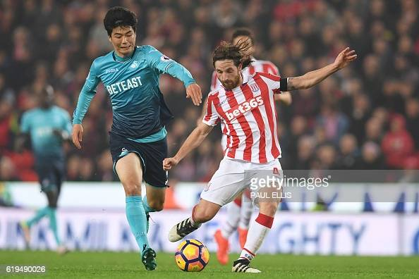 Swansea City's South Korean midfielder Ki SungYueng vies with Stoke City's Welsh midfielder Joe Allen during the English Premier League football...