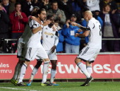 Swansea City's Spanish defender Chico Flores is congratulated by team mates after he scored a goal during a Premier League football match between...