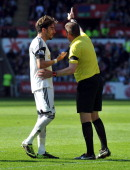 Swansea City's Spanish defender Chico Flores is sent off by referee Phil Dowd for a tackle on Chelsea's German striker Andre Schurrle during the...