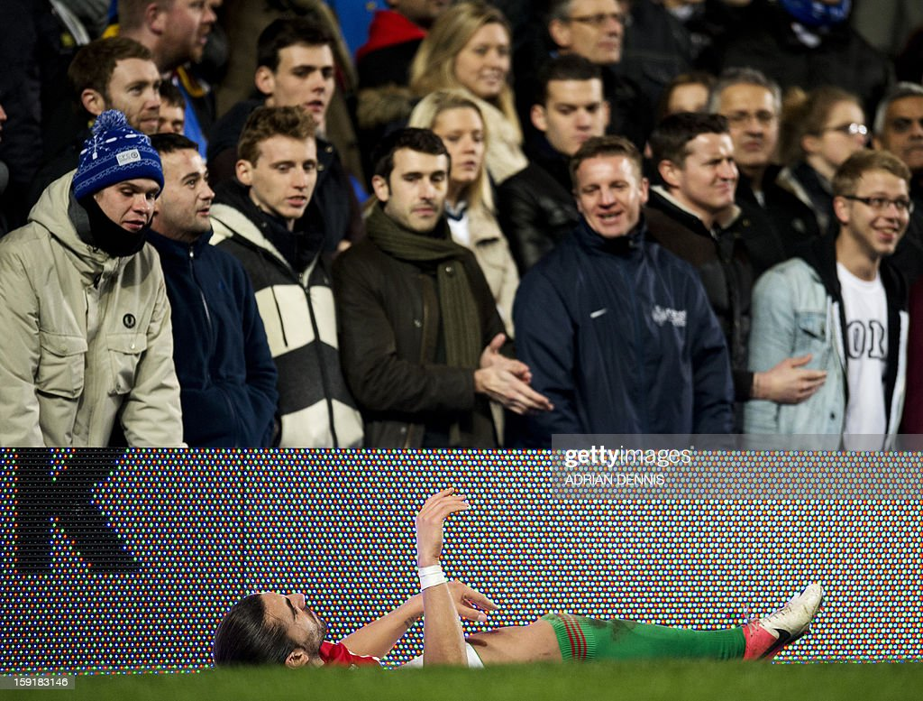 """Swansea City's Spanish defender Chico Flores lies injured in front of Chelsea fans during the English League Cup first leg semi-final football match between Chelsea and Swansea City at Stamford Bridge in London on January 9, 2013. Swansea won the match 2-0. USE. No use with unauthorized audio, video, data, fixture lists, club/league logos or """"live"""" services. Online in-match use limited to 45 images, no video emulation. No use in betting, games or single club/league/player publications."""