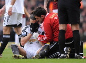 Swansea City's Spanish defender Chico Flores sits injured after a challenge by West Ham United's English striker Andy Carroll during the English...