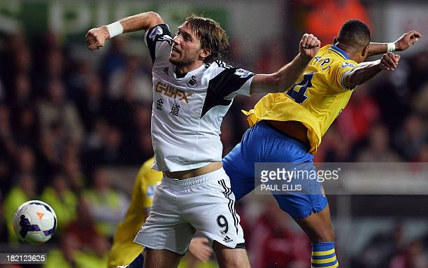 Swansea City's Spanish midfielder Miguel Michu challenges Arsenal's German forward Serge Gnabry during the English Premier League football match...