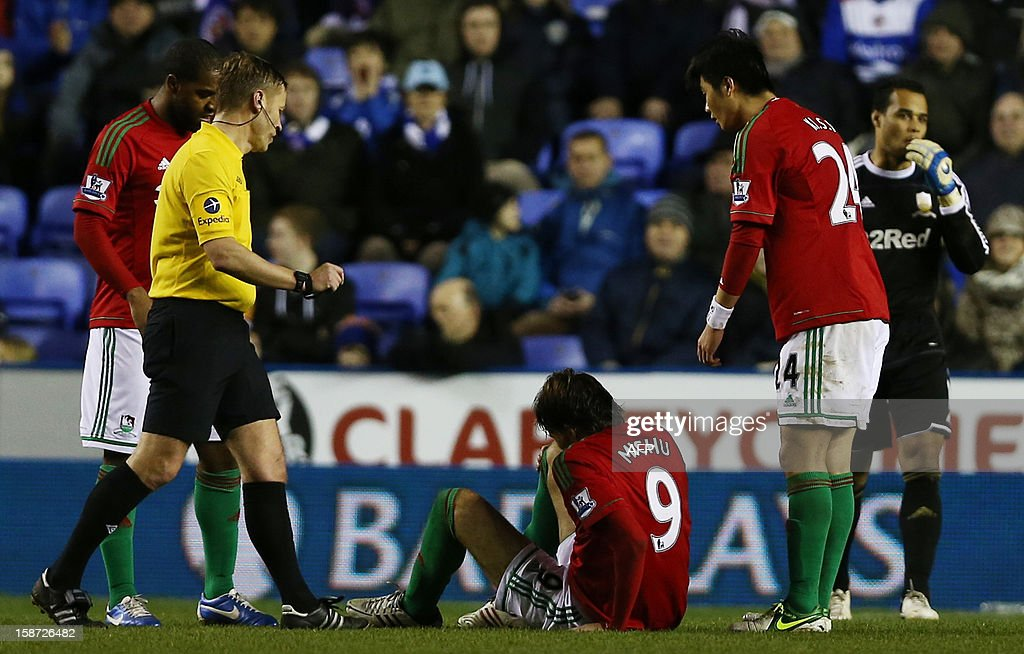 "Swansea city's Spanish midfielder Miguel Michu (C) lies on the floor after taking a knock during the English Premier League football match between Reading and Swansea City at at The Madejski Stadium, in Reading, southern England on December 26, 2012. AFP PHOTO/ANDREW COWIE USE. No use with unauthorized audio, video, data, fixture lists, club/league logos or ""live"" services. Online in-match use limited to 45 images, no video emulation. No use in betting, games or single club/league/player publications"