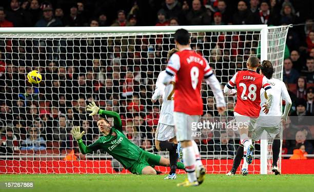 Swansea City's Spanish midfielder Miguel Michu scores past Arsenal's Polish goalkeeper Wojciech Szczesny during the English Premier League football...