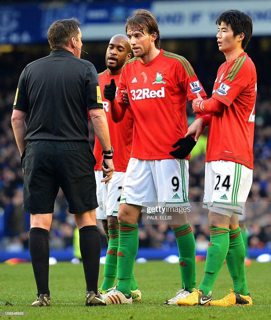 """Swansea City's Spanish midfielder Miguel Michu (2-R) speaks to referee Phil Dowd during the English Premier League football match between Everton and Swansea City at Goodison Park in Liverpool on January 12, 2013. AFP PHOTO/Paul ELLIS- RESTRICTED TO EDITORIAL USE. No use with unauthorized audio, video, data, fixture lists, club/league logos or """"live"""" services. Online in-match use limited to 45 images, no video emulation. No use in betting, games or single club/league/player publications."""