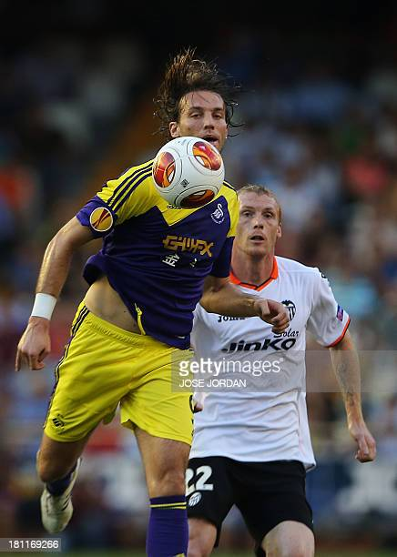 Swansea City's Spanish midfielder Miguel Michu vies with Valencia's French defender Jeremy Mathieu during the UEFA Europa league football match...