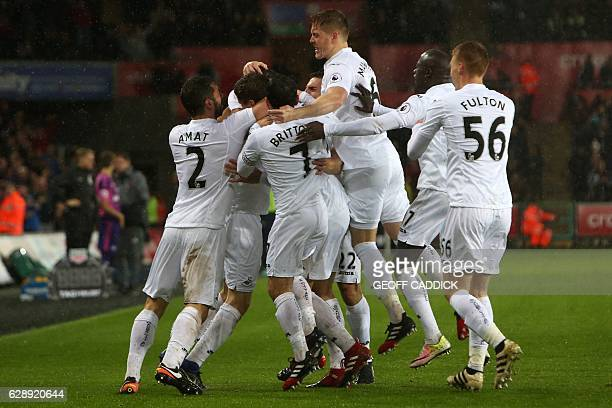 Swansea City's Spanish striker Fernando Llorente celebrates with teammates after scoring their second goal during the English Premier League football...