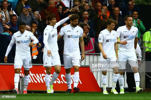 Swansea City's Spanish striker Fernando Llorente celebrates with teammates after scoring the opening goal of the English Premier League football...