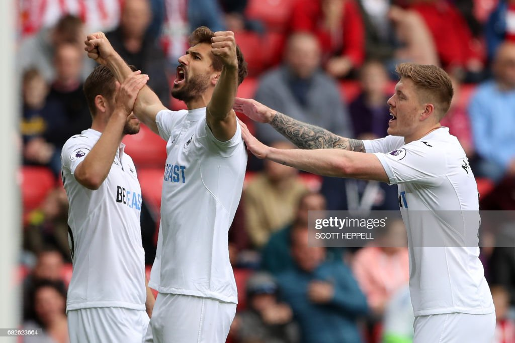 Swansea City's Spanish striker Fernando Llorente (C) celebrates with Swansea City's Icelandic midfielder Gylfi Sigurdsson (L) and Swansea City's English defender Alfie Mawson (R) after scoring the opening goal of the English Premier League football match between Sunderland and Swansea City at the Stadium of Light in Sunderland, north-east England on May 13, 2017. / AFP PHOTO / Scott Heppell / RESTRICTED TO EDITORIAL USE. No use with unauthorized audio, video, data, fixture lists, club/league logos or 'live' services. Online in-match use limited to 75 images, no video emulation. No use in betting, games or single club/league/player publications. /