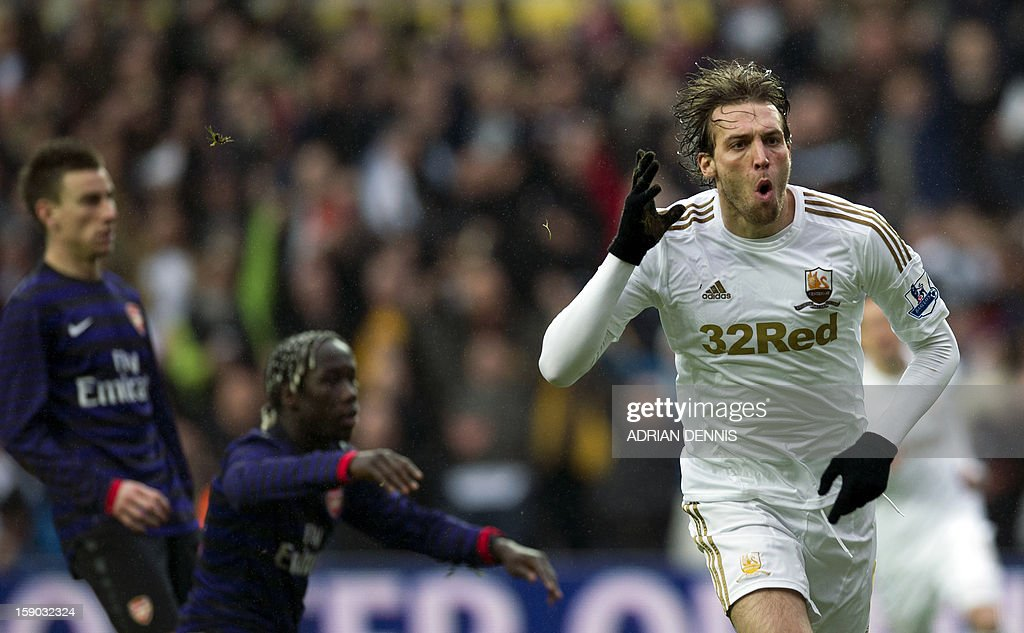 "Swansea City's Spanish striker Miguel Michu (R) runs to celebrate after scoring the opening goal against Arsenal during the FA Cup third round football match at the Liberty Stadium in Swansea, Wales on January 6, 2013. The game ended with a 2-2 draw. USE. No use with unauthorized audio, video, data, fixture lists, club/league logos or ""live"" services. Online in-match use limited to 45 images, no video emulation. No use in betting, games or single club/league/player publications."