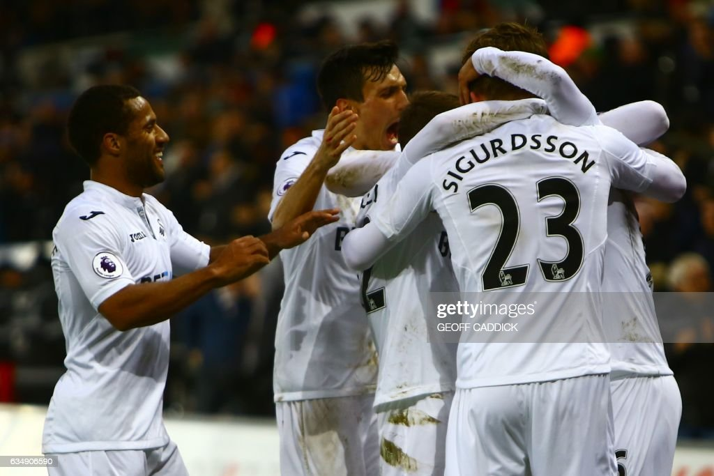 Swansea City's Swedish defender Martin Olsson (R) celebrates with teammates after scoring their second goal during the English Premier League football match between Swansea City and Leicester City at The Liberty Stadium in Swansea, south Wales on February 12, 2017. / AFP / Geoff CADDICK / RESTRICTED TO EDITORIAL USE. No use with unauthorized audio, video, data, fixture lists, club/league logos or 'live' services. Online in-match use limited to 75 images, no video emulation. No use in betting, games or single club/league/player publications. /