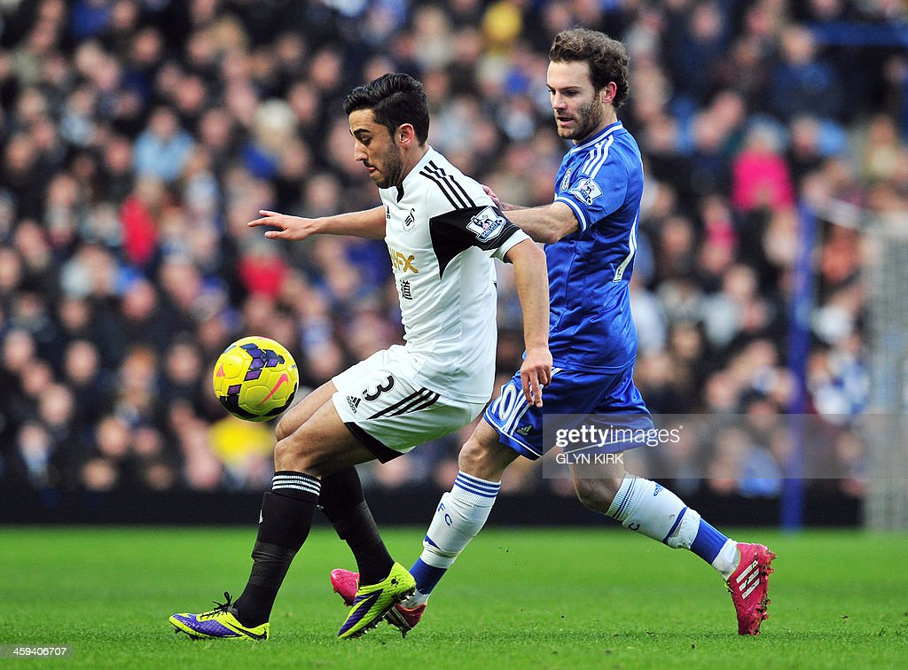 Swansea City's Welsh defender Neil Taylor (L) vies with Chelsea's Spanish midfielder Juan Mata (R) during the English Premier League football match between Chelsea and Swansea City at Stamford Bridge in London on December 26, 2013. USE. No use with unauthorized audio, video, data, fixture lists, club/league logos or live services. Online in-match use limited to 45 images, no video emulation. No use in betting, games or single club/league/player publications.