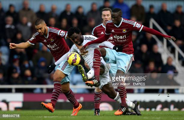 Swansea City's Wilfried Bony is tackled by a combination of West Ham United's Winston Reid and teammate Cheikhou Kouyate
